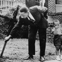 Martin Luther King, Jr removes a burned cross from his yard in 1960. The boy is his son.